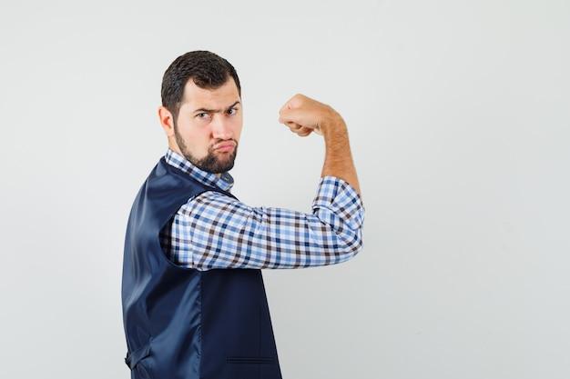 Młody człowiek pokazuje swoje mięśnie w koszuli, kamizelce i wygląda potężnie.