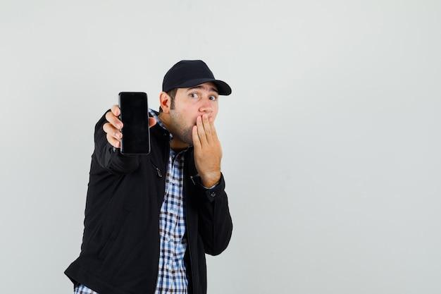 Młody człowiek pokazuje telefon komórkowy ręką na ustach w koszuli, kurtce, czapce i patrząc zaskoczony. przedni widok.