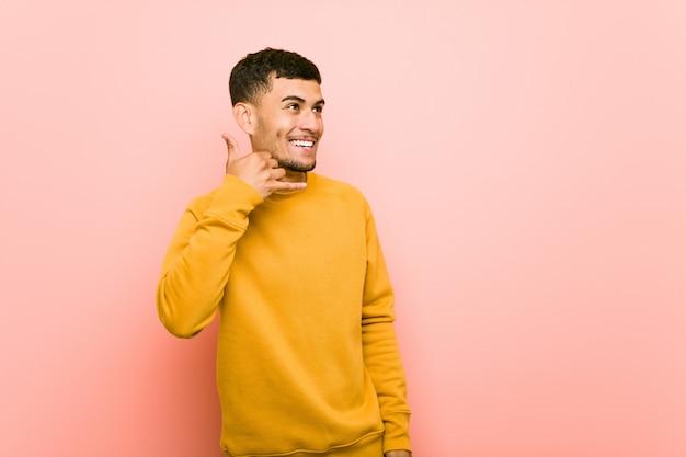 Młody człowiek pokazuje telefon komórkowy wezwania gest z palcami