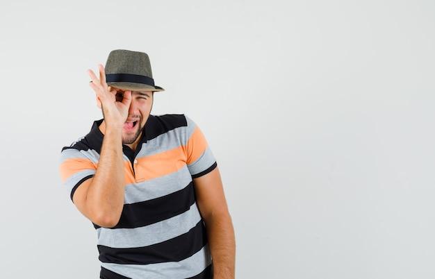 Młody człowiek pokazuje znak ok na oku w koszulce, kapeluszu i wygląda zaciekawiony