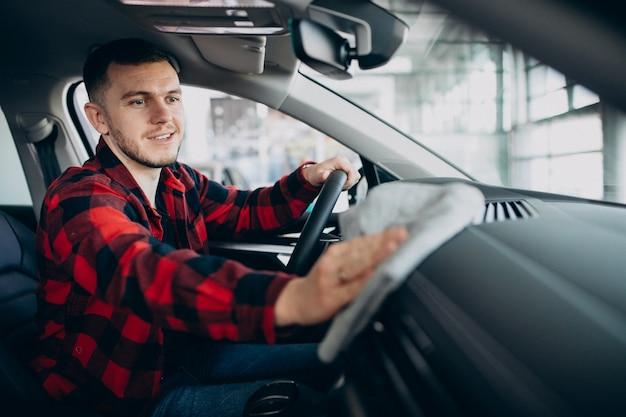 Młody człowiek poleruje swój samochód szmatą