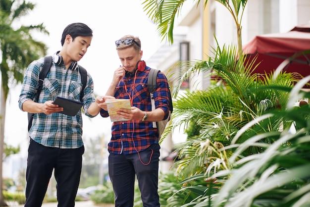 Młody człowiek pomaga przyjacielowi znaleźć punkt docelowy na mapie, gdy giną w mieście