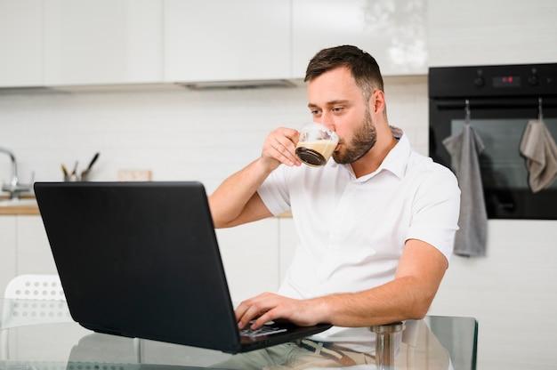 Młody człowiek popija kawę podczas gdy patrzejący laptop