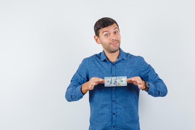 Młody człowiek posiadający dolara w niebieskiej koszuli i patrząc na szczęście. przedni widok.