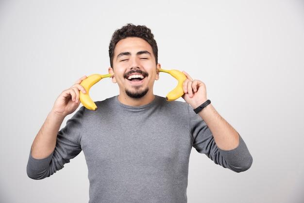 Młody człowiek posiadający dwa świeże banany.