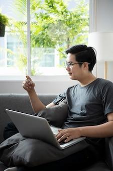 Młody człowiek posiadający kartę kredytową i przy użyciu komputera przenośnego na zakupy online w domu.