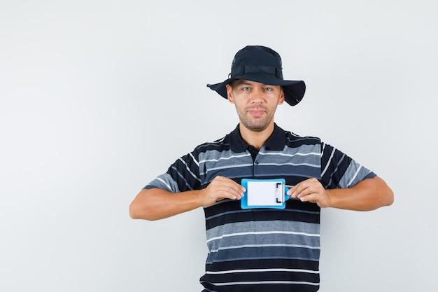 Młody człowiek posiadający mini schowek w koszulce, kapeluszu i patrząc pozytywnie, widok z przodu.