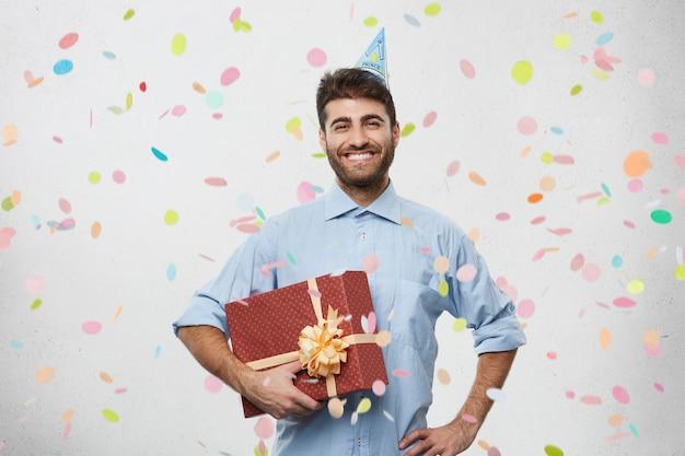 Młody człowiek posiadający obecny otoczony konfetti