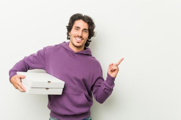 Młody człowiek posiadający pakiet pizzy, uśmiechając się wesoło, wskazując palcem wskazującym daleko.