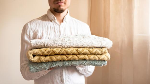 Młody człowiek posiadający świeże ręczniki składane.