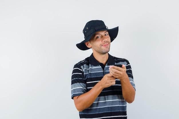 Młody człowiek posiadający telefon komórkowy w t-shirt, kapelusz i patrząc wesoły, widok z przodu.
