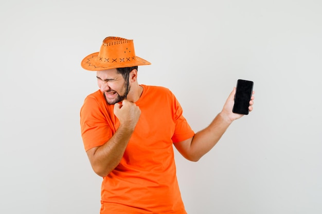 Młody człowiek posiadający telefon komórkowy z gestem zwycięzcy w pomarańczowy t-shirt, kapelusz i patrząc szczęśliwy, widok z przodu.