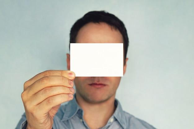 Młody człowiek posiadający wizytówkę. biznesmen zamyka oczy wizytówkę. puste dla tekstu. biała wizytówka w ręku. makieta pozioma