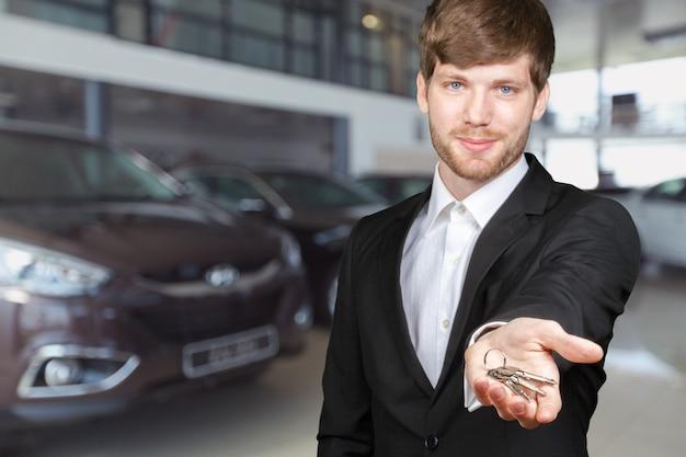 Młody człowiek pośrednik w obrocie nieruchomościami lub kierownik sprzedaży pokazujący klucze do samochodu lub domu