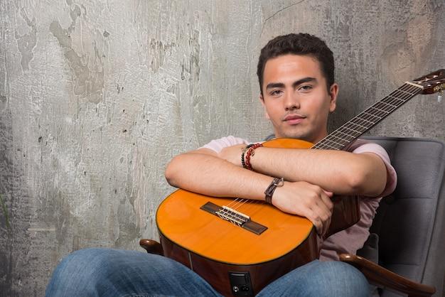 Młody człowiek pozowanie na kamery, trzymając gitarę.