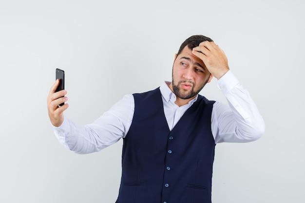 Młody człowiek pozuje podczas robienia selfie w koszuli i kamizelce i wygląda przystojny