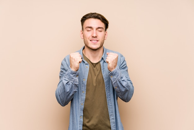 Młody człowiek pozuje podnoszącą pięść, czuje się szczęśliwy i pomyślny