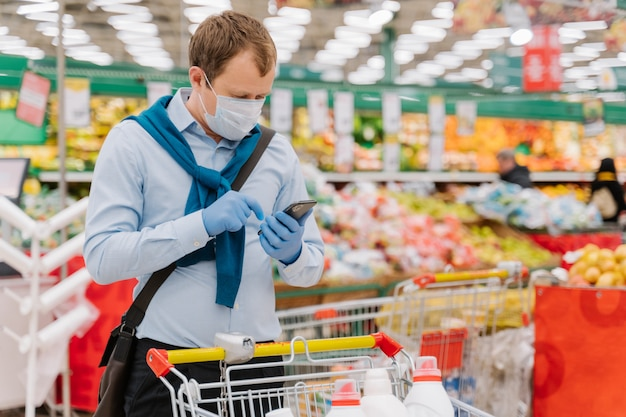 Młody człowiek pozuje w sklepie spożywczym podczas pandemii koronawirusa, nosi ochronną maskę medyczną i rękawiczki