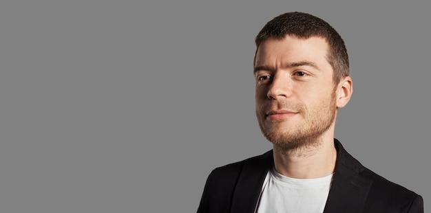 Młody człowiek pozuje z czarną kurtką i białą koszulką