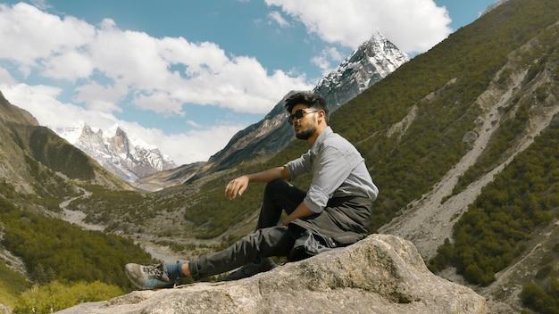 Młody człowiek pozuje z górami