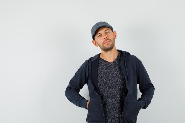 Młody człowiek pozuje z rękami w kieszeniach w t-shirt, kurtkę, czapkę i wygląda elegancko.