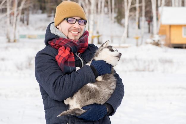 Młody człowiek pozuje z szczeniakiem w zimie