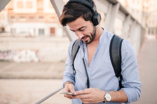 Młody człowiek pozycja na bridżowym używa smartphone