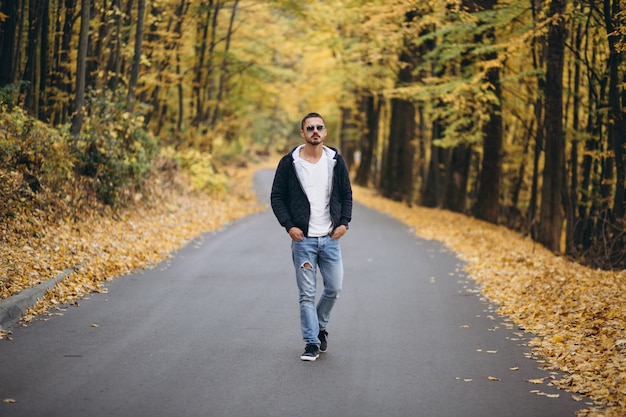 Młody człowiek pozycja na drodze w jesień parku