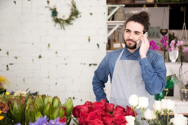 Młody człowiek pozycja za pięknymi kwiatami opowiada na telefonie komórkowym