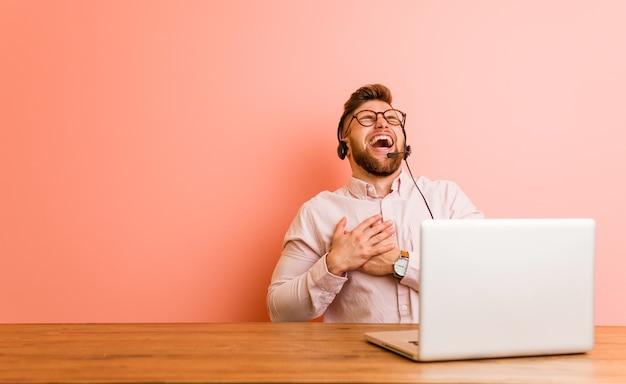 Młody człowiek pracujący w call center, śmiejąc się, trzymając ręce na sercu, pojęcie szczęścia.