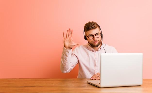 Młody człowiek pracujący w call center uśmiechnięty wesoły pokazując numer pięć palcami.