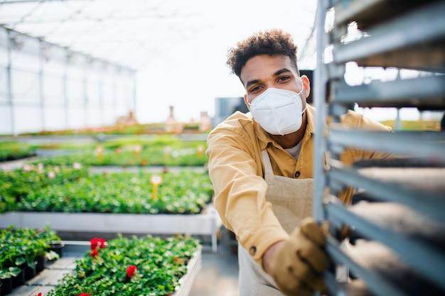 Młody człowiek pracujący w szklarni w centrum ogrodniczym, koncepcja koronawirusa.