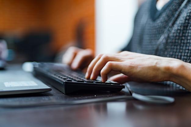 Młody człowiek pracuje na klawiaturze