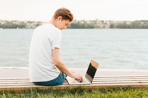 Młody człowiek pracuje na laptopie nad jeziorem