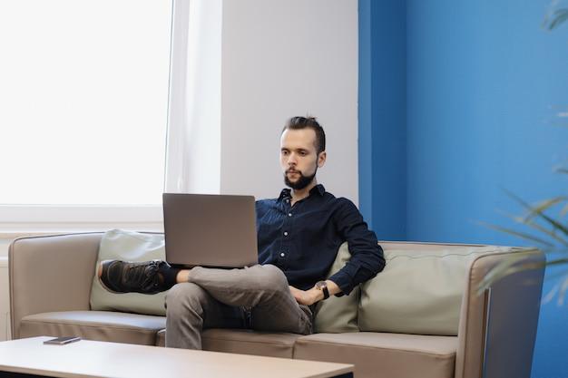 Młody człowiek pracuje na laptopie podczas gdy siedzący na kanapie w biurze