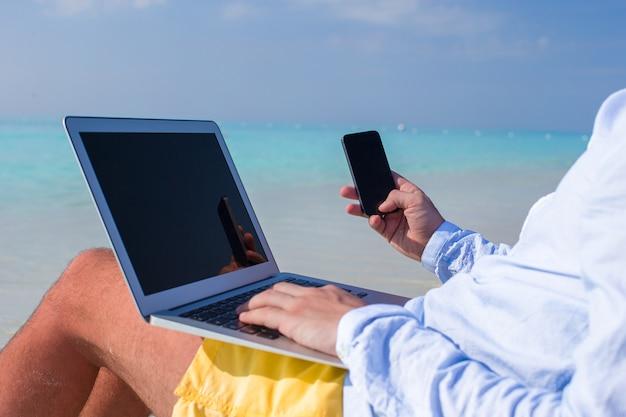 Młody człowiek pracuje na laptopie przy tropikalną plażą