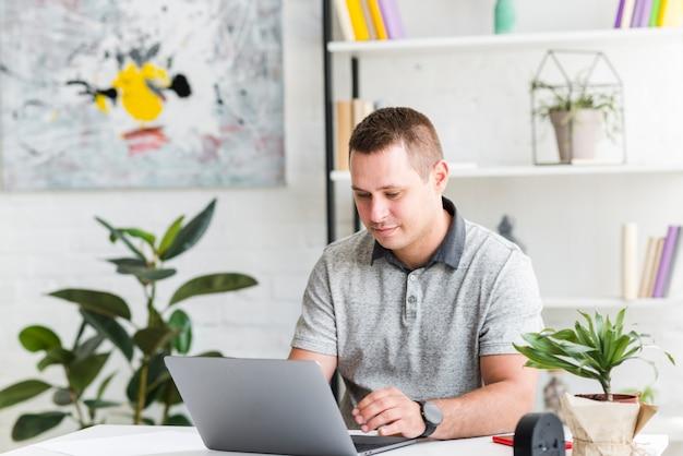 Młody człowiek pracuje na laptopie w domu
