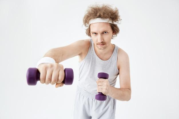 Młody człowiek pracuje na mięśnie ramion, trening z hantlami