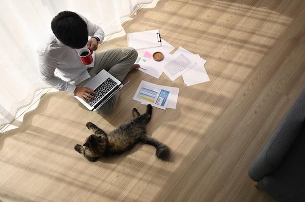 Młody człowiek pracuje na swoim laptopie z kotem w wygodnym domu.