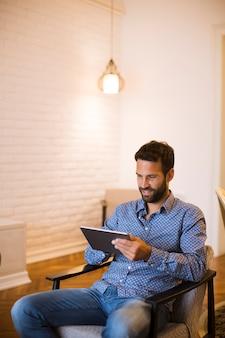 Młody człowiek pracuje od domu na cyfrowej pastylce