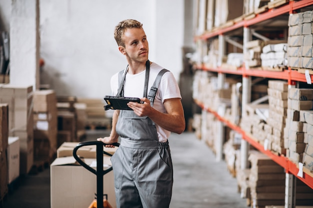 Młody człowiek pracuje przy magazynem z pudełkami