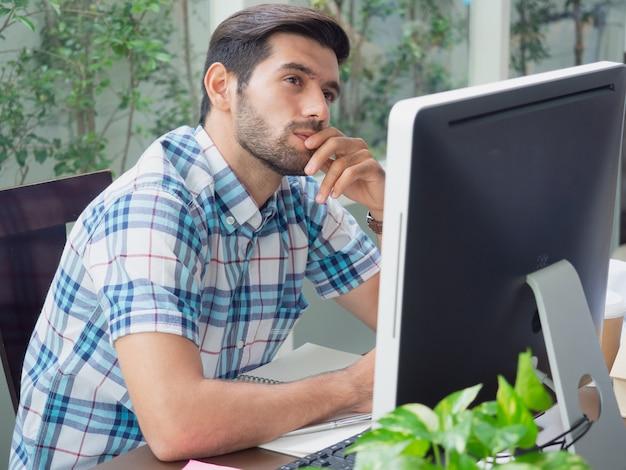 Młody człowiek pracuje w domu i myśli coś