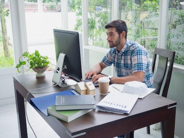 Młody człowiek pracuje w domu z kawą i gazetą