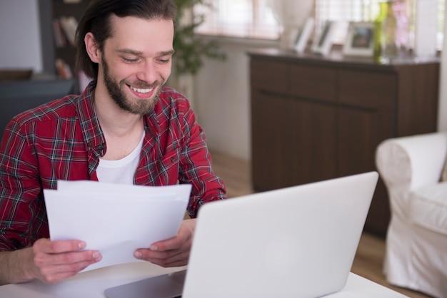 Młody człowiek pracuje w domu ze swoim laptopem
