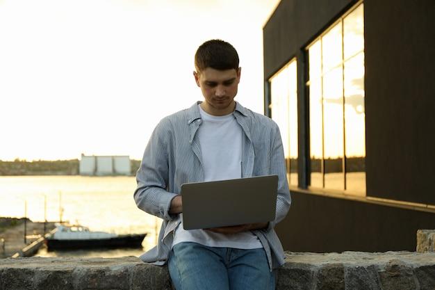 Młody człowiek pracuje w laptopie plenerowym. wolny strzelec