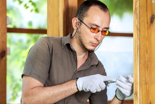 Młody człowiek pracuje z drewnem