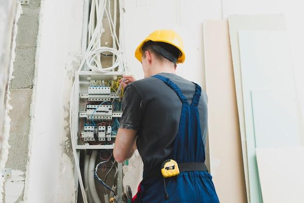 Młody człowiek pracuje z drutami przy switcher