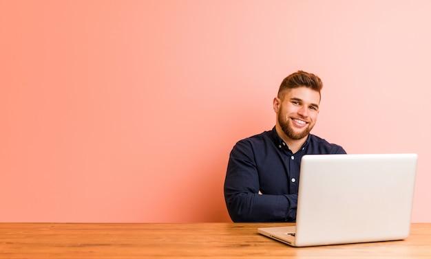 Młody człowiek pracuje z jego laptopem który czuje się pewnie, krzyżuje ręki z determinacją.