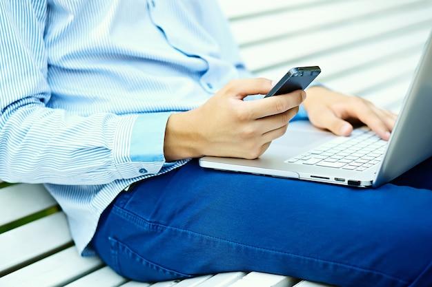 Młody człowiek pracuje z laptopem, mężczyzna ręki na notebooku, biznesowa osoba w przypadkowych ubraniach na ulicie