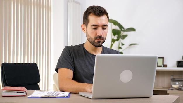 Młody człowiek pracuje z laptopem w jego dokumentacji biznesowej. biznesmen w miejscu pracy.